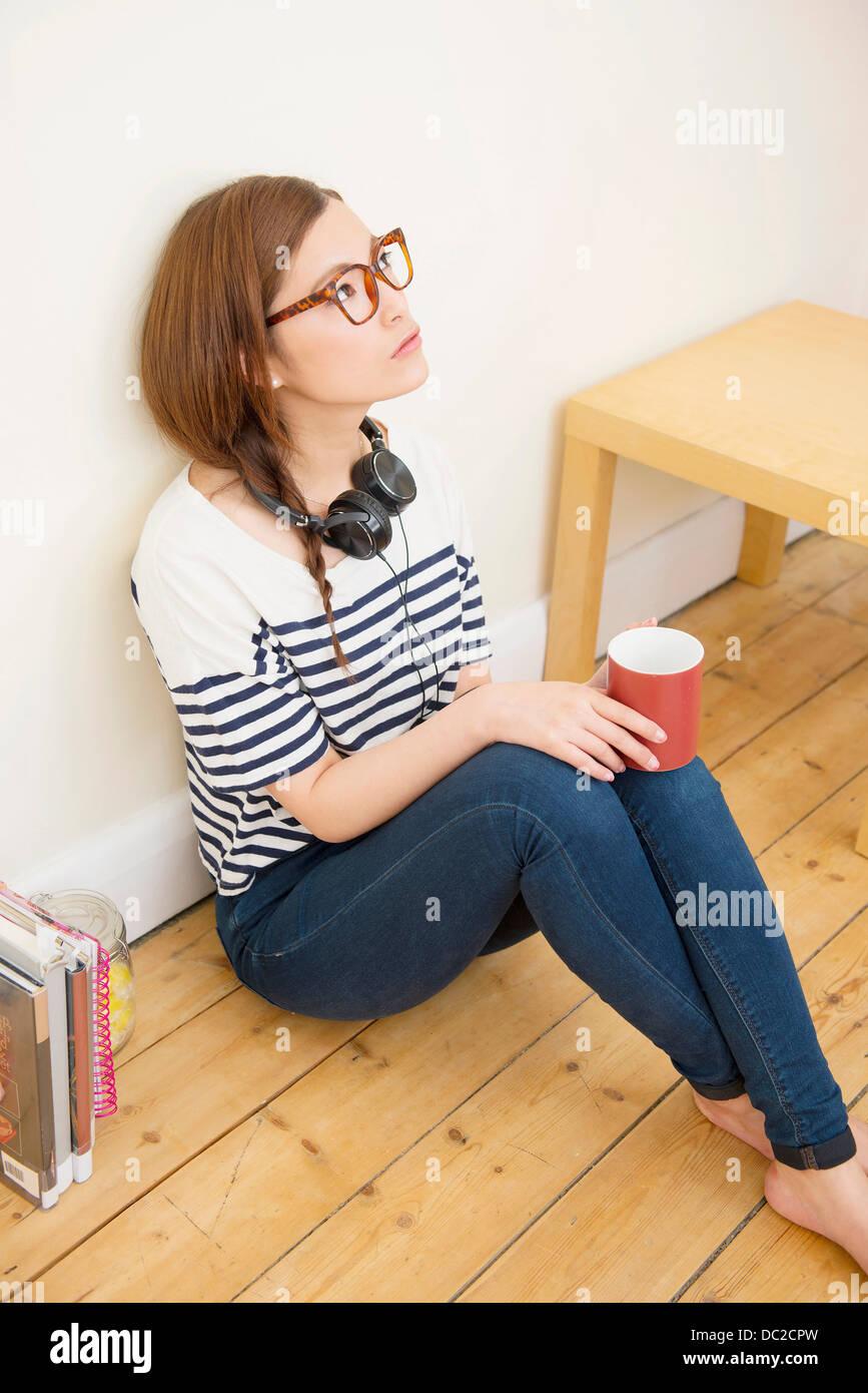 Woman with mug looking upward - Stock Image