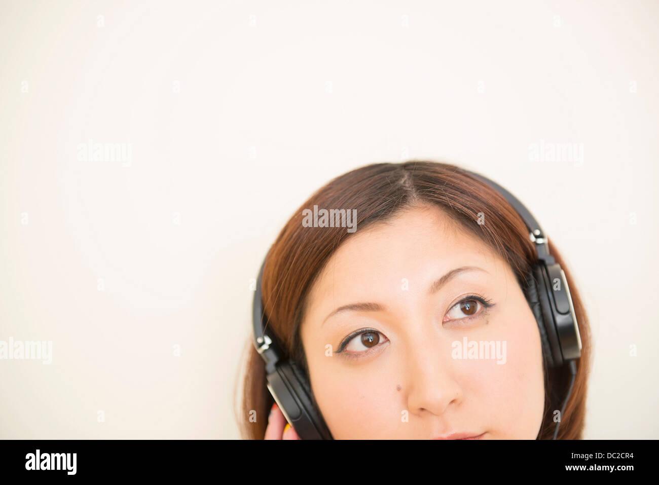 Woman wearing earphones looking upward - Stock Image
