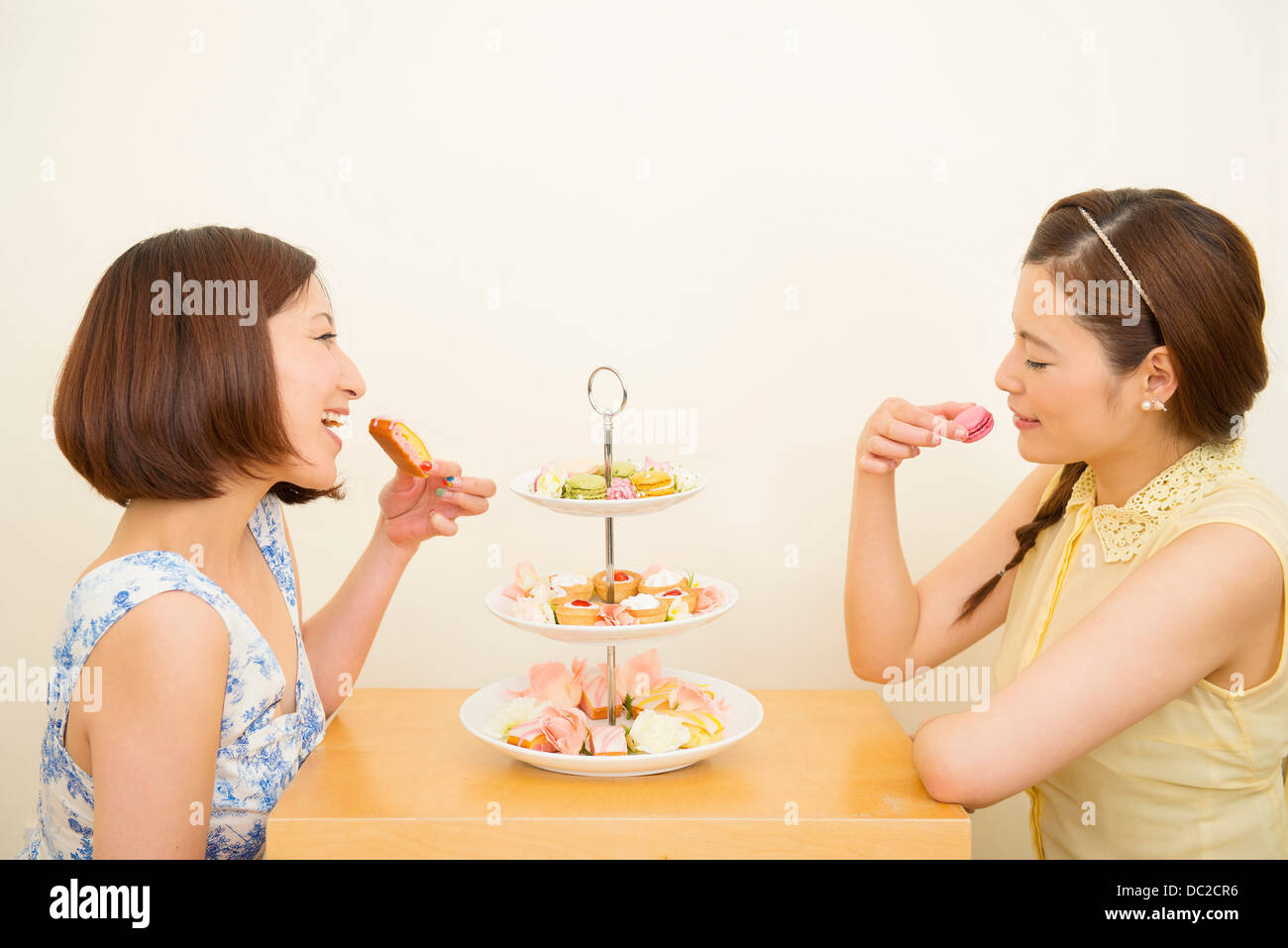 Two happy women enjoying dessert from three tiered cake stand - Stock Image