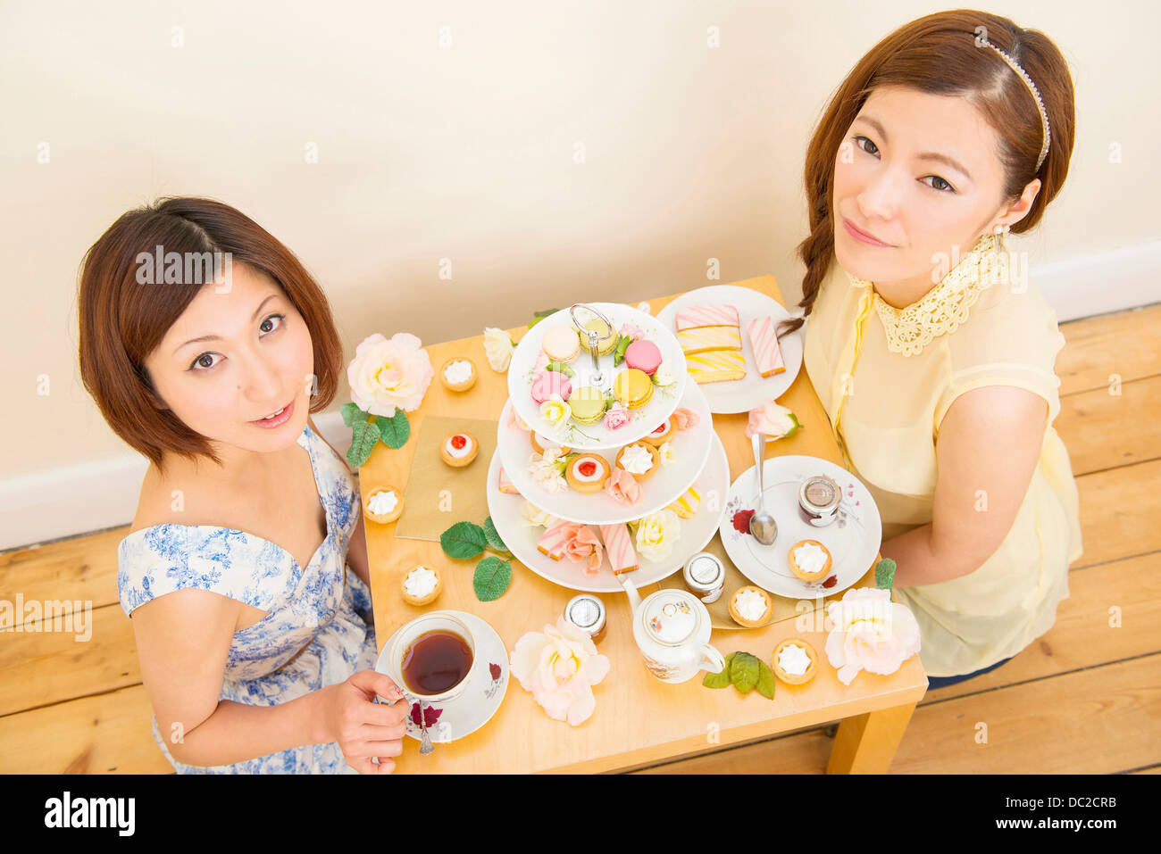 Two women looking up from their teatime treats - Stock Image
