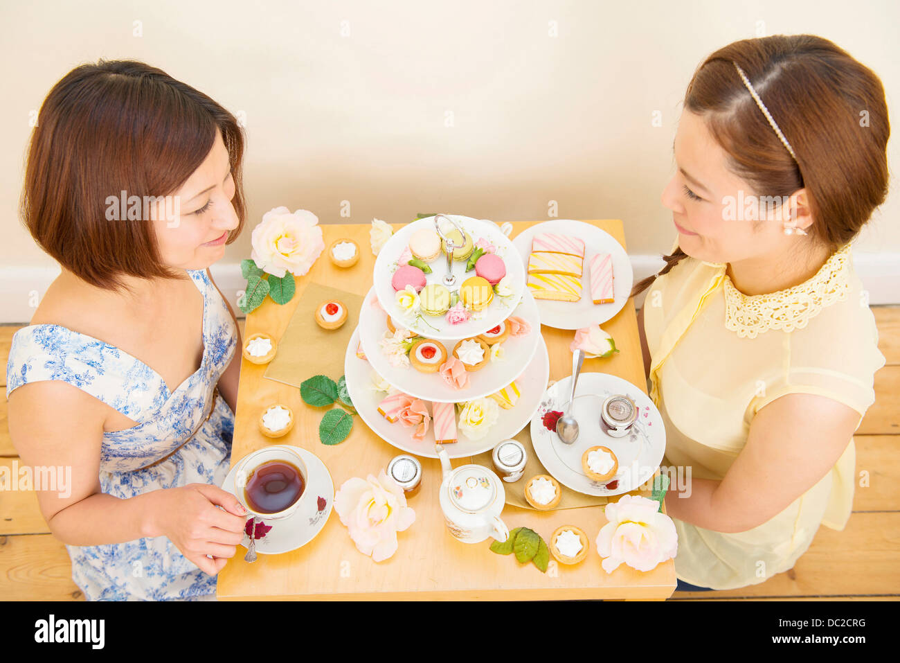 Two women having tea and teatime treats - Stock Image