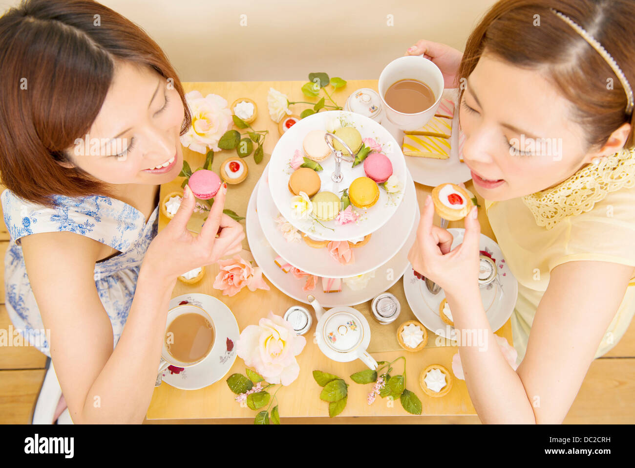Two happy women indulging in sweet cakes - Stock Image