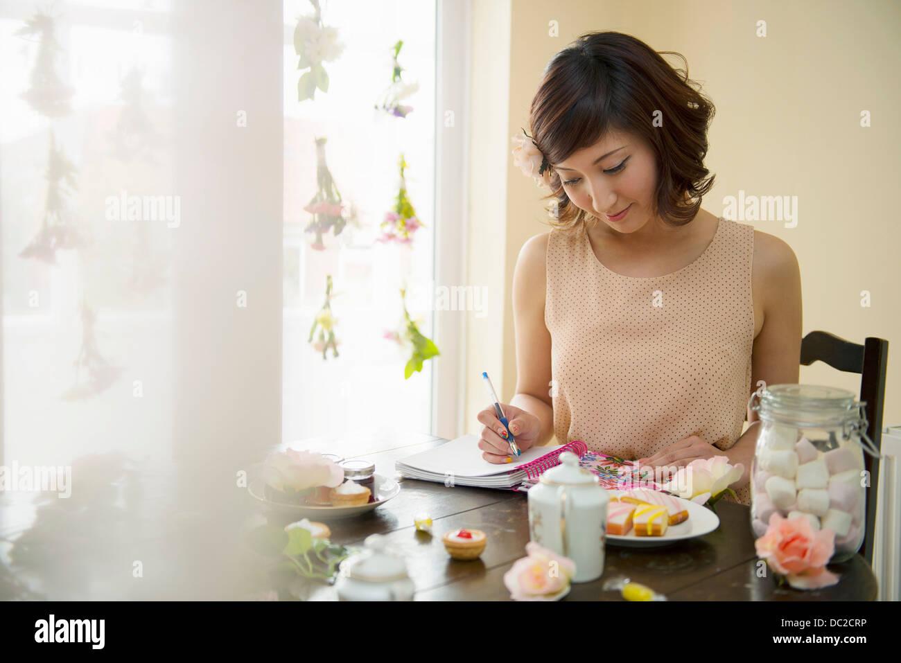Woman writing notes at tea time - Stock Image