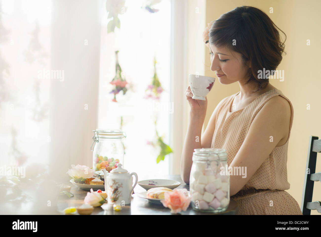 Woman looking down at tea cup - Stock Image