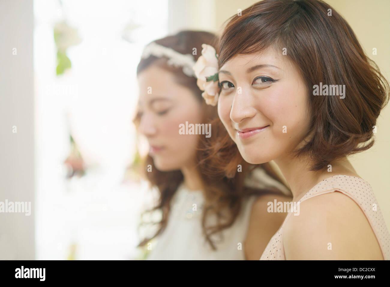 Woman smiling looking sideways at camera - Stock Image