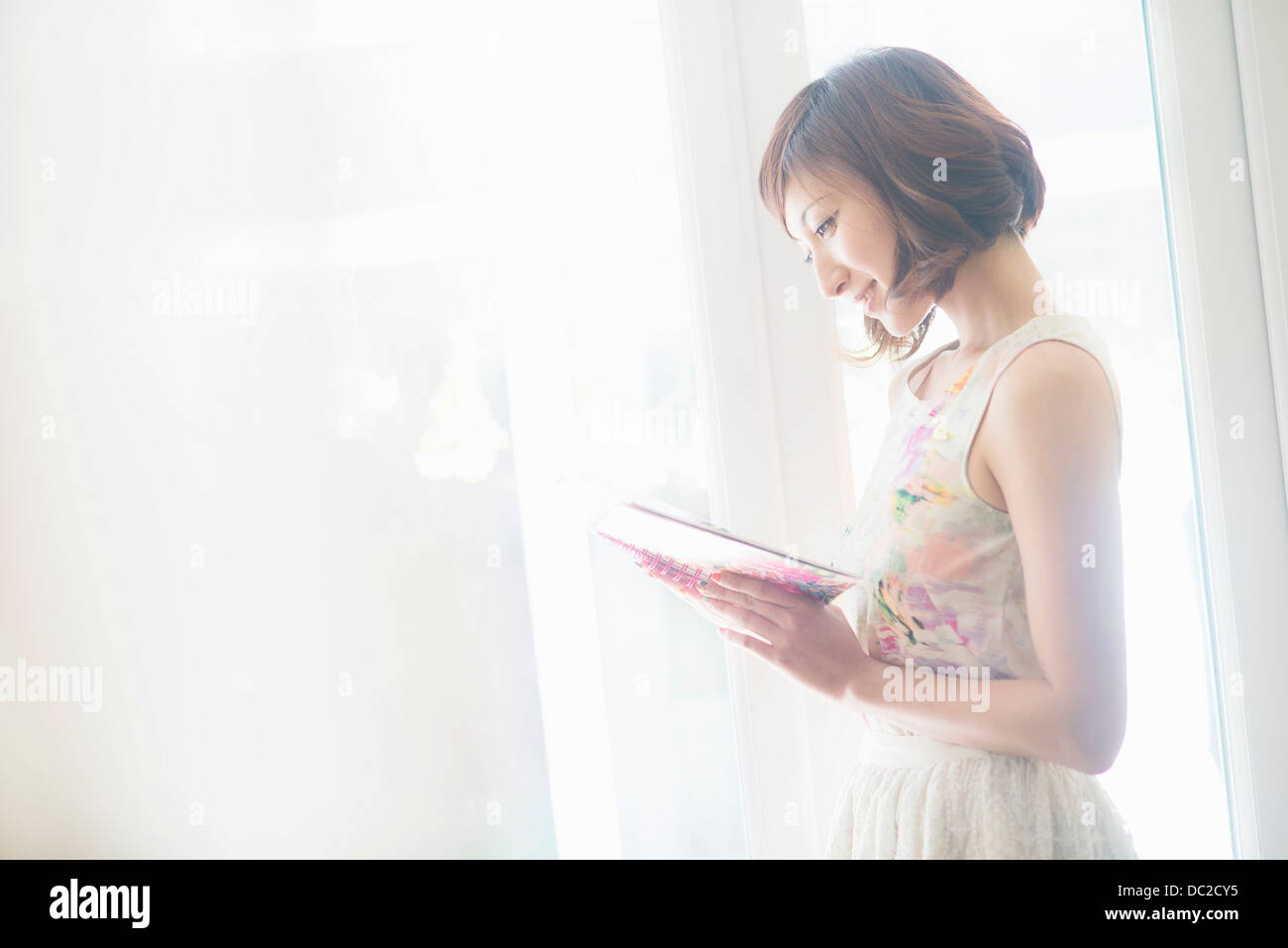 Woman smiling and reading book - Stock Image