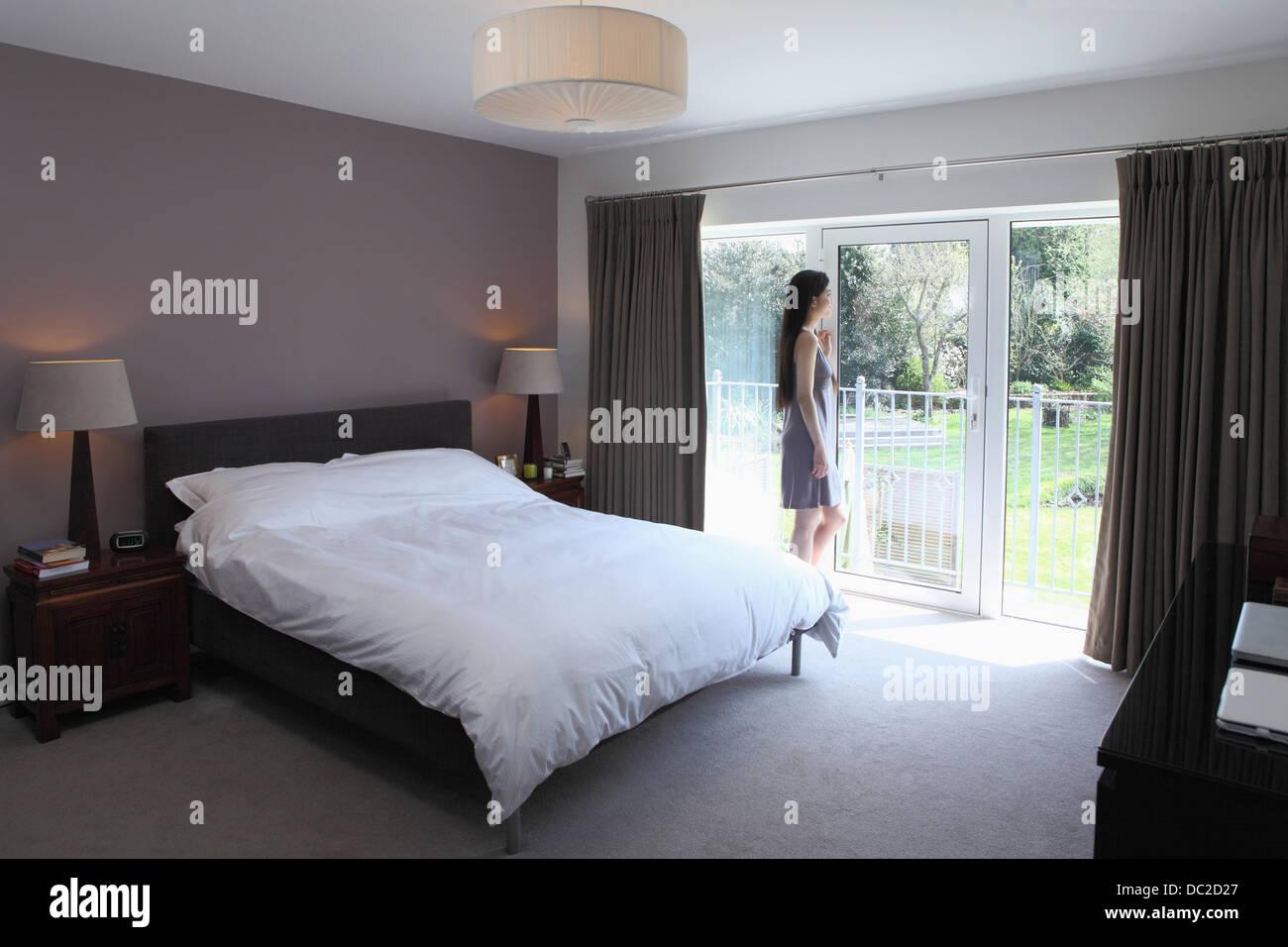Woman looking through glass door of bedroom Stock Photo