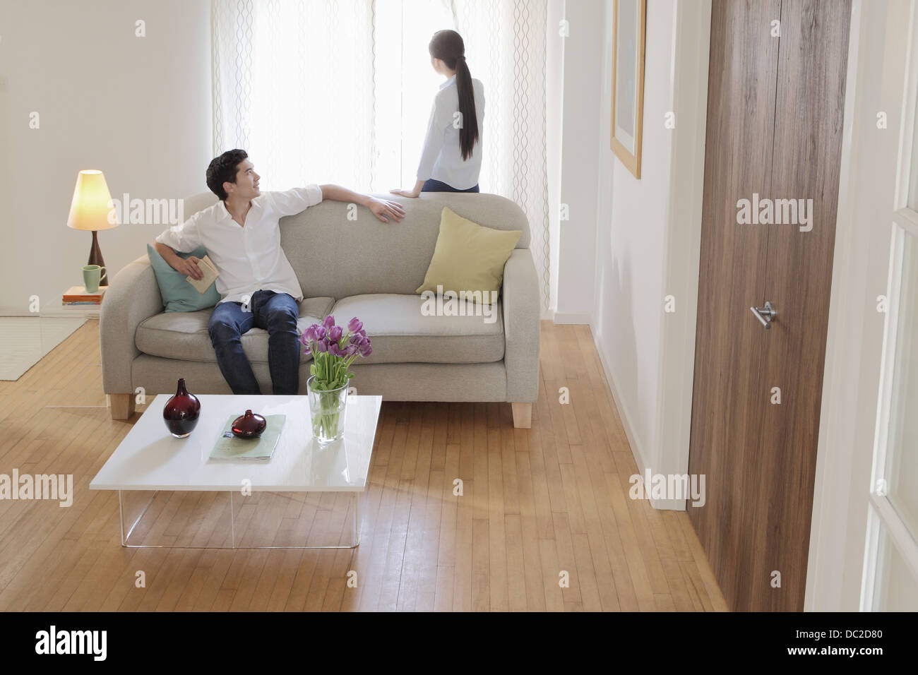 Husband turning round on sofa to look at wife - Stock Image
