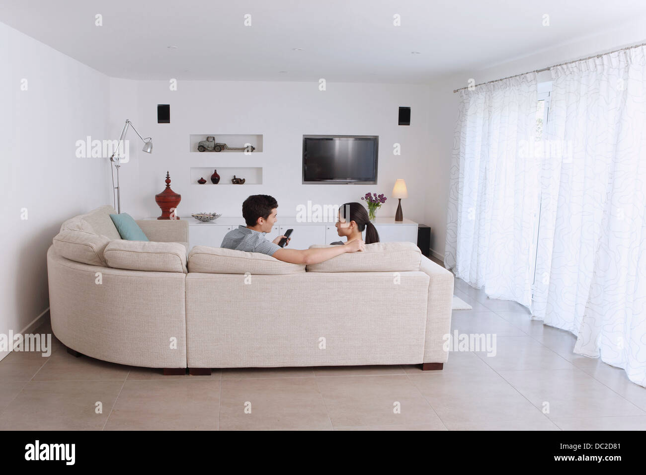 Husband and wife relaxing on corner sofa in living room - Stock Image