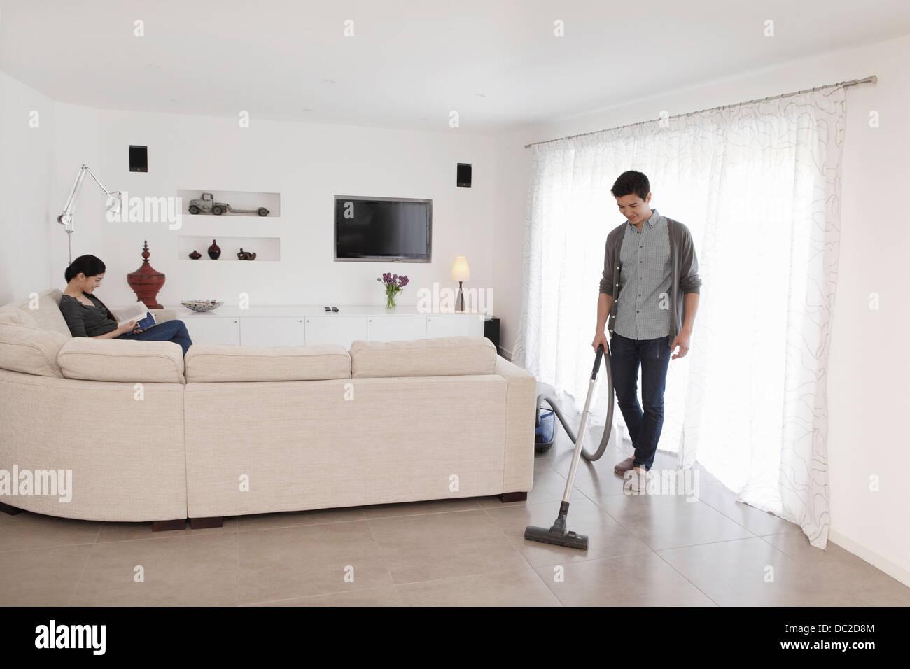 Man vacuuming living room floor - Stock Image