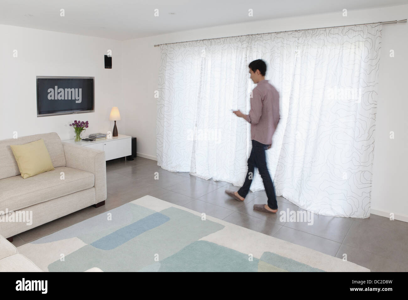 Man with mobile phone walking past curtains - Stock Image