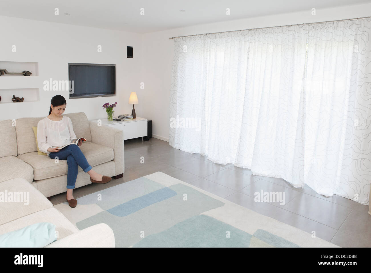 Woman reading in living room - Stock Image