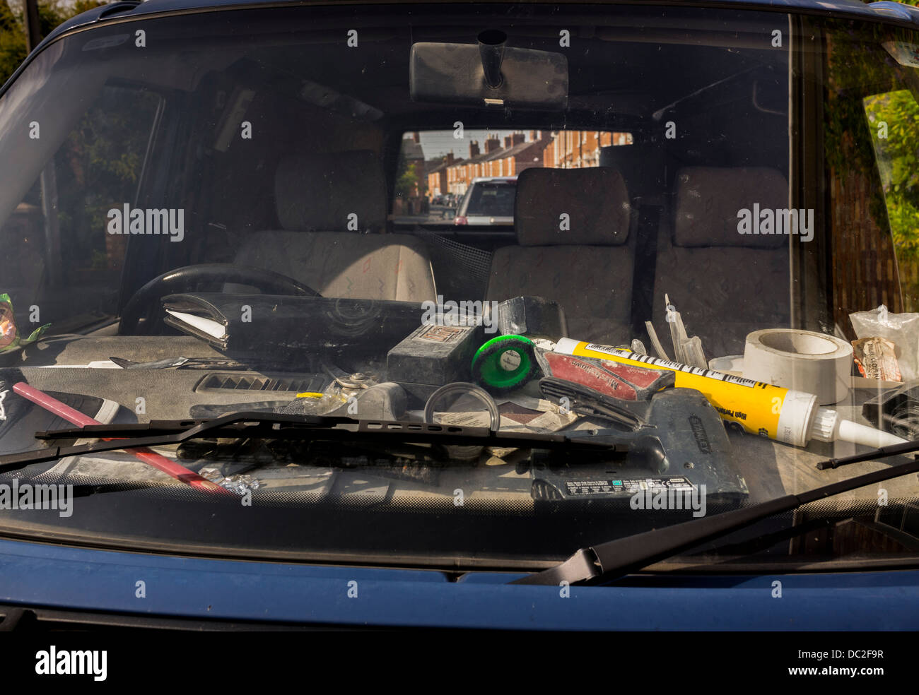 DIRTY ,DUSTY, DISORGANISED, DASH BOARD OF BUILDERS VAN WITH JUMBLE OF TOOLS ,TAPE MASTIC, NOTE BOOK, PENCIL,MESSY. - Stock Image