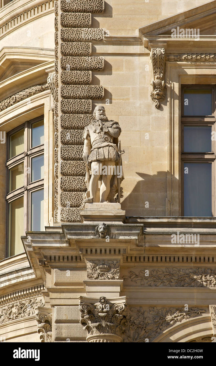 Decorative elements of an angle of the Richelieu wing of the Louvre Palace in Paris, France. Statue of Sully, by - Stock Image