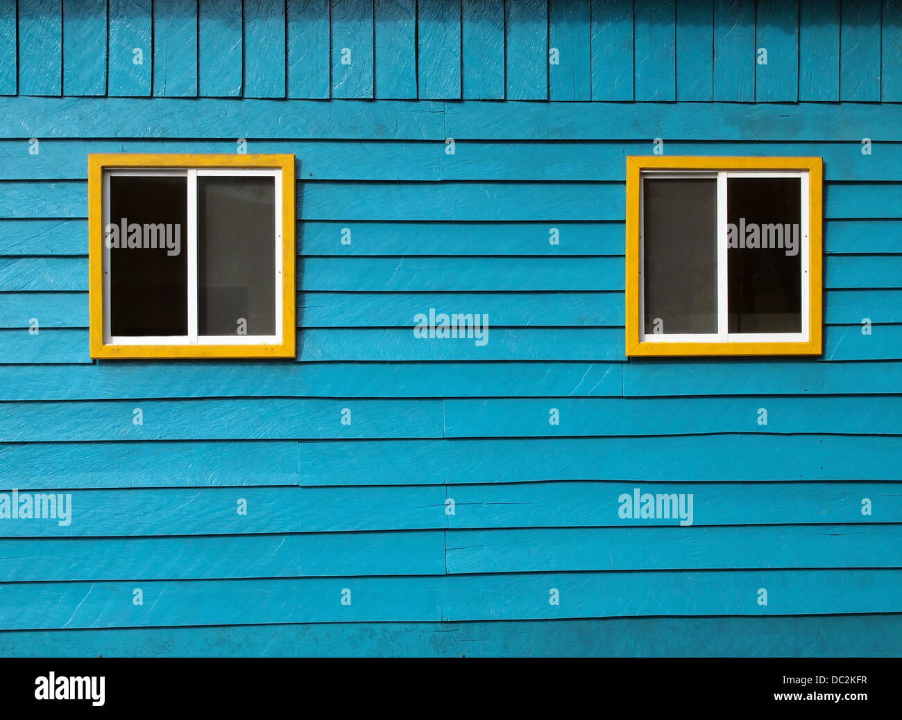 Rustic blue wooden wall with two windows - Stock Image