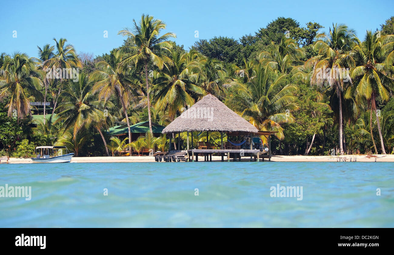 Tropical beach home paradise with palapa over the water - Stock Image