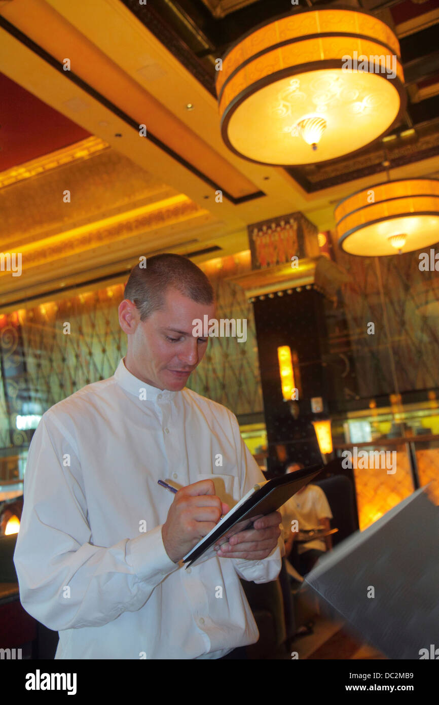Florida Sunrise Fort Ft. Lauderdale Sawgrass Mills Mall Grand Lux Cafe restaurant inside interior man waiter writing - Stock Image