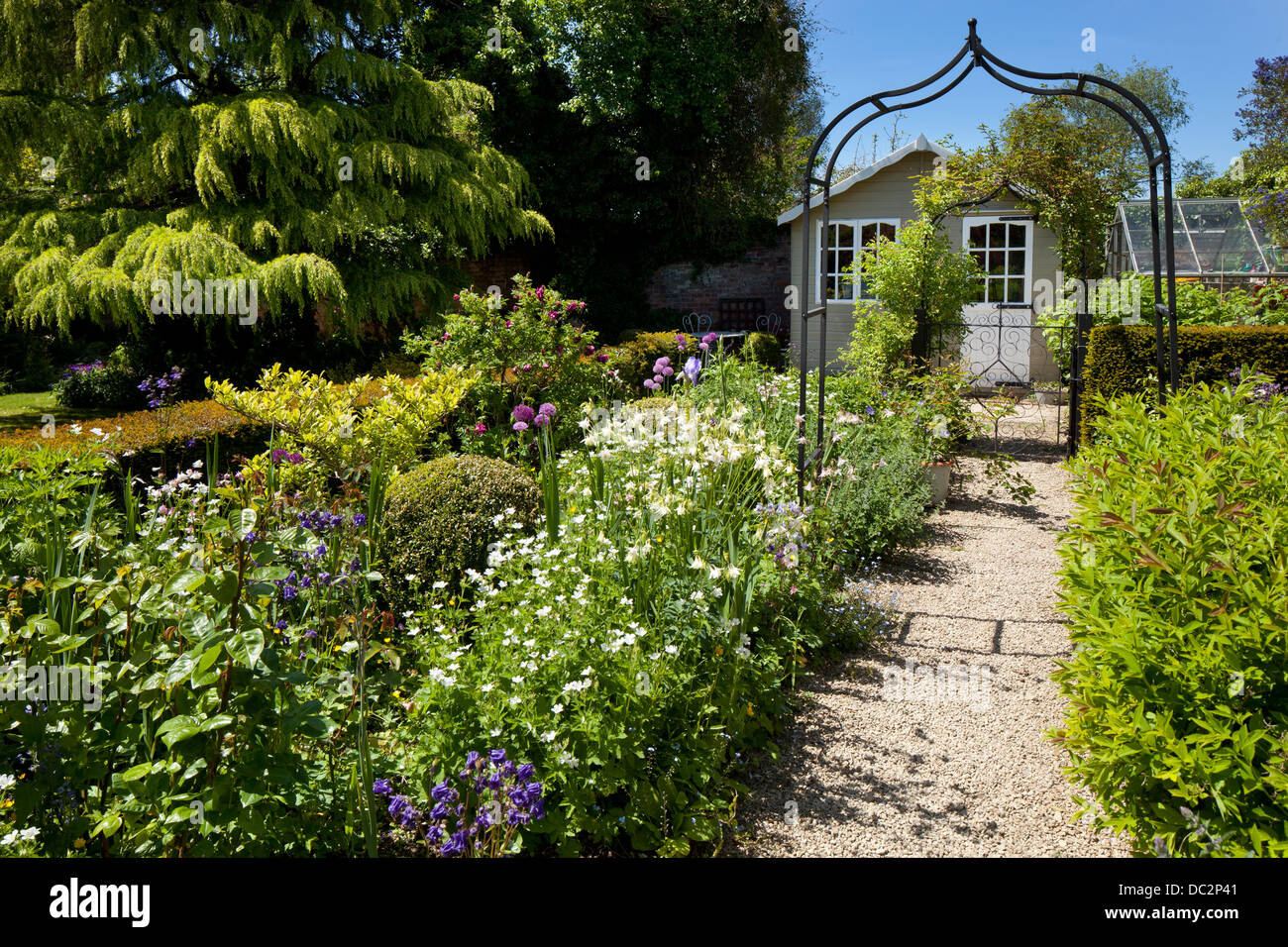 Metal arch leading on a gravel path to flower boarder and summerhouse on English garden, England - Stock Image