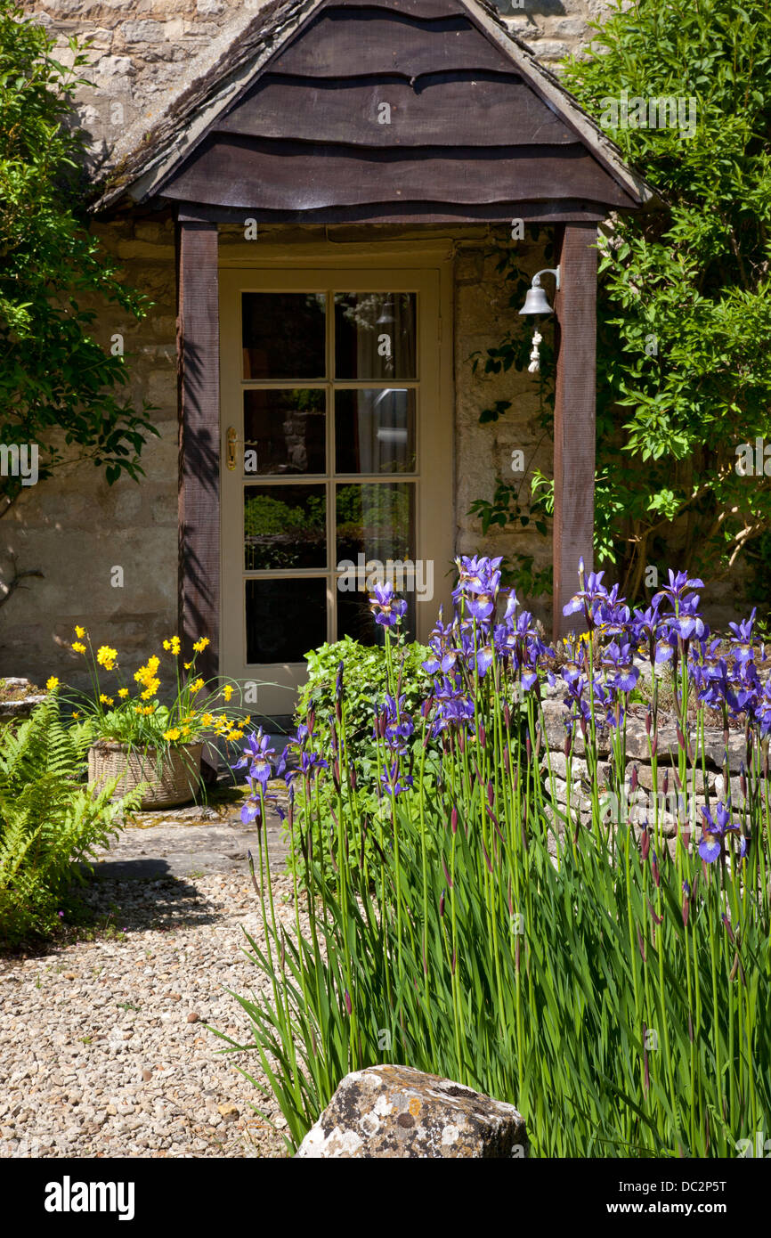 Porch Of House With Gravel Path And Purple Iris Flowers In English Garden,  England