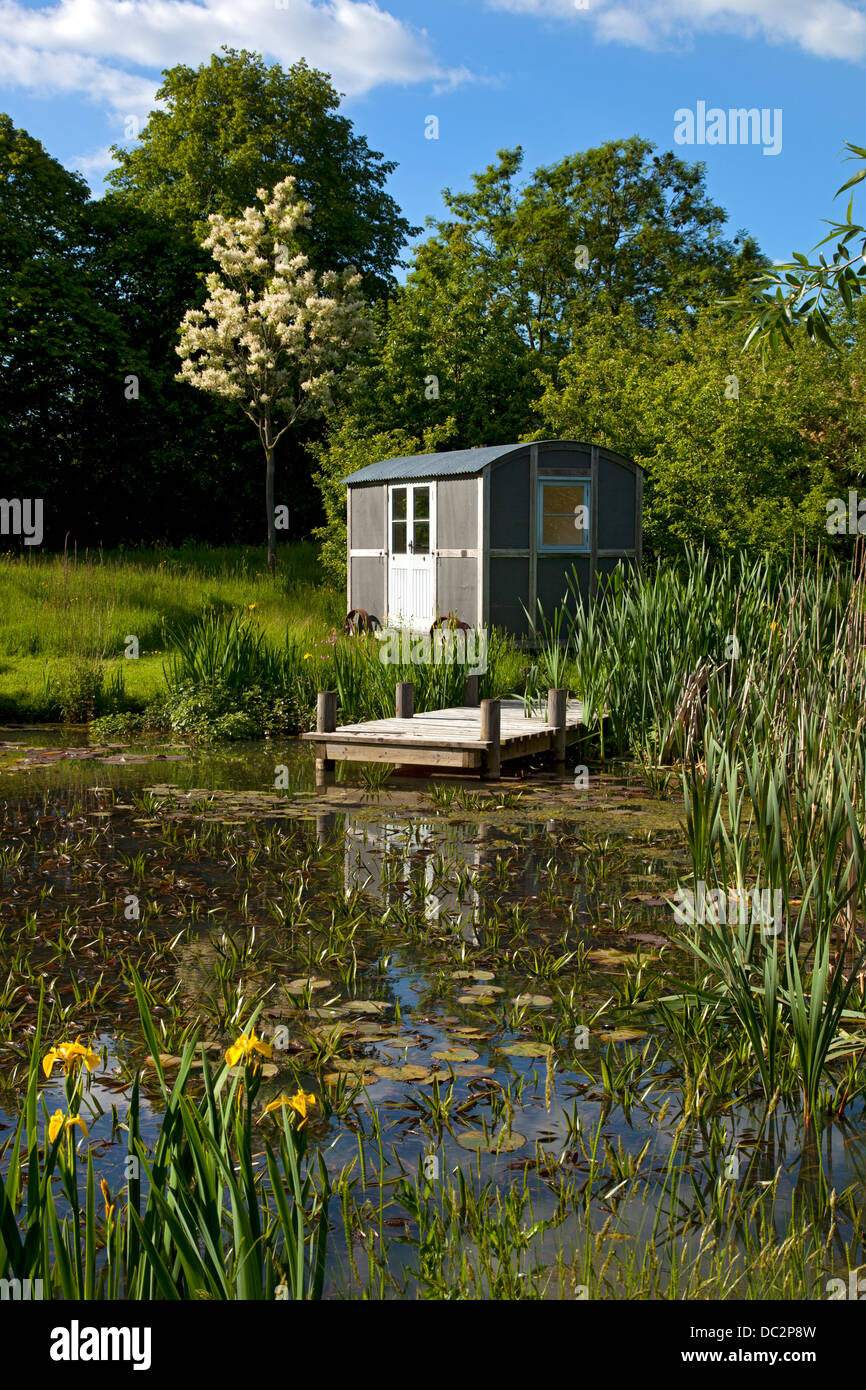Shepherds Hut on wheels in garden by pond, England - Stock Image