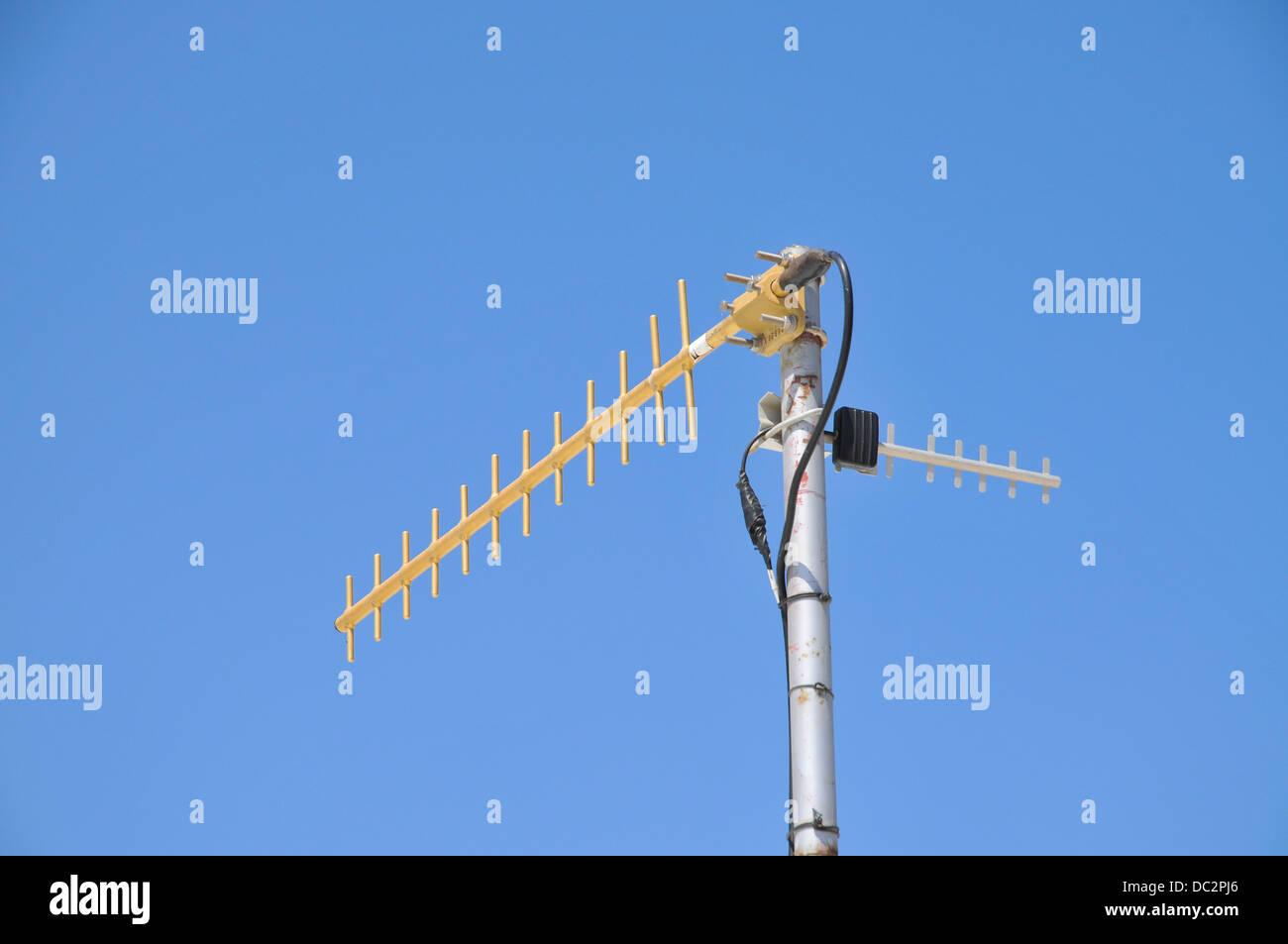 RF Antenna on blue sky background - Stock Image
