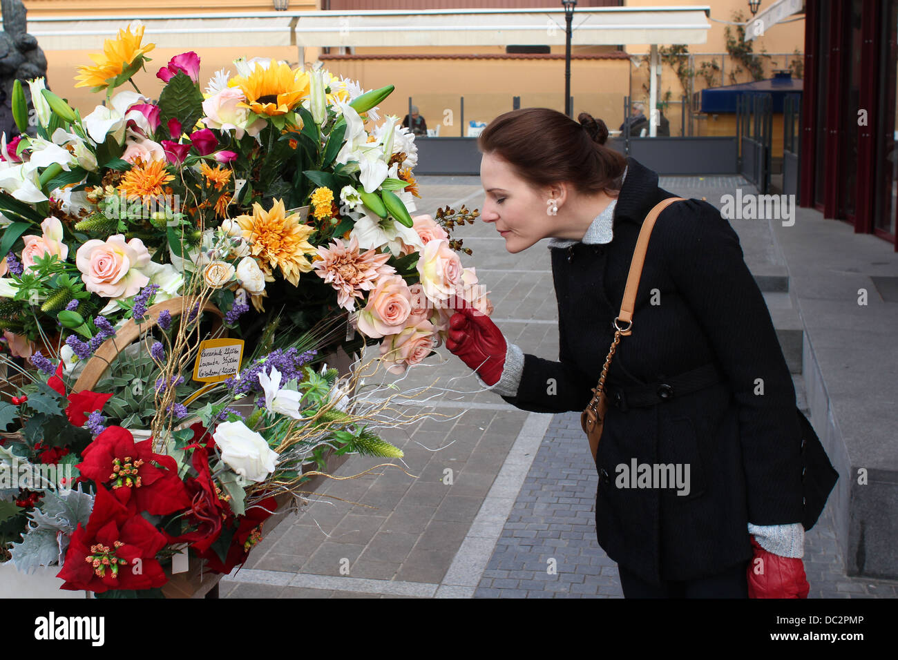 Woman smelling flower at market Stock Photo