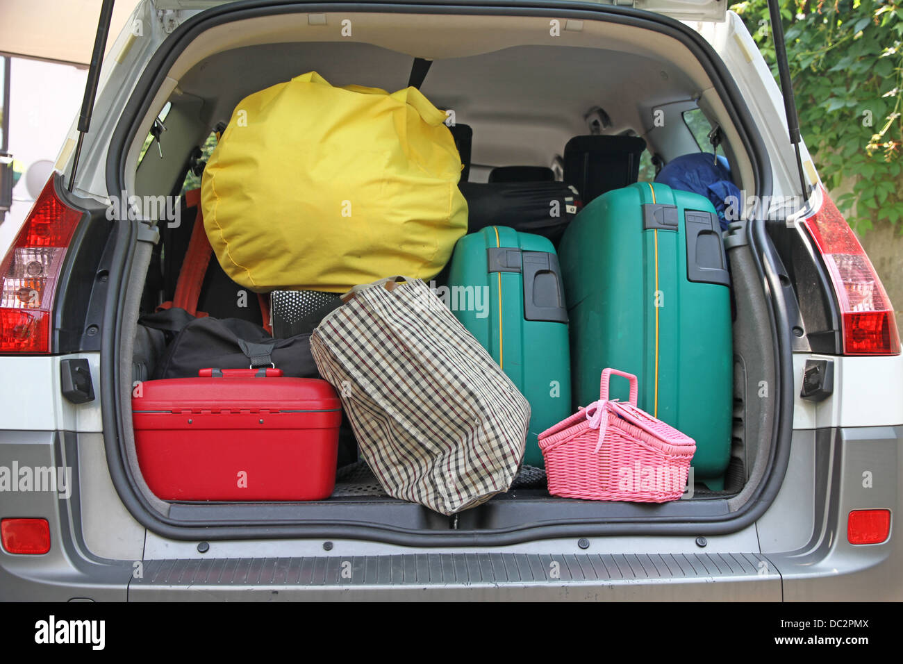two green suitcases and many bags in the trunk of the car ready to depart for the holidays - Stock Image