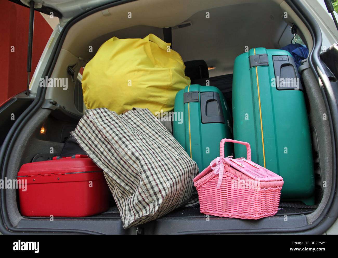 two green suitcase and a pink trash bag in the trunk of the family car ready for the holidays - Stock Image