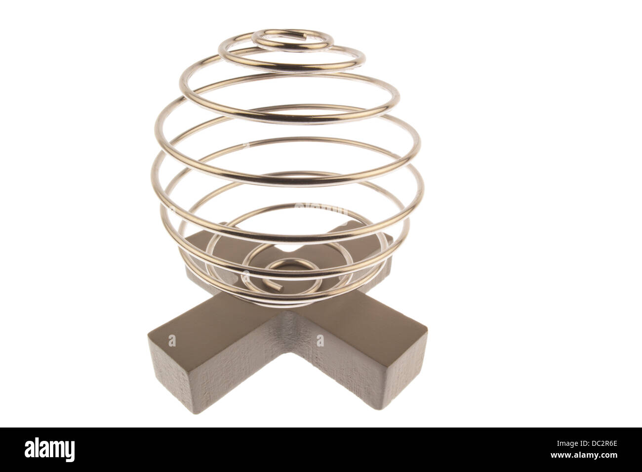 Iron wire tangled up into a spiral ball resulting in a shiny chrome sphere and standing on top of a gray cross and Stock Photo