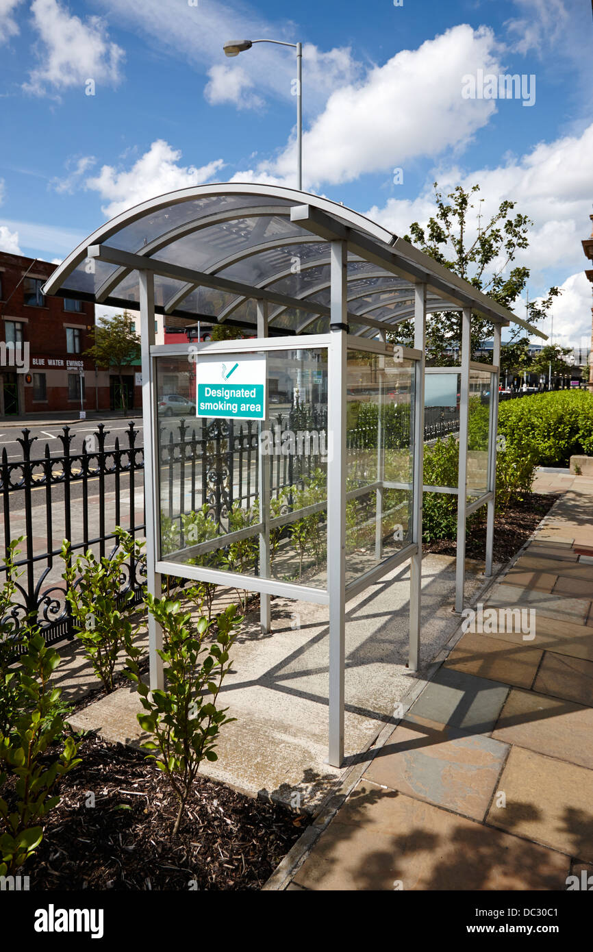 designated smoking area shelter outside an office building in the UK - Stock Image