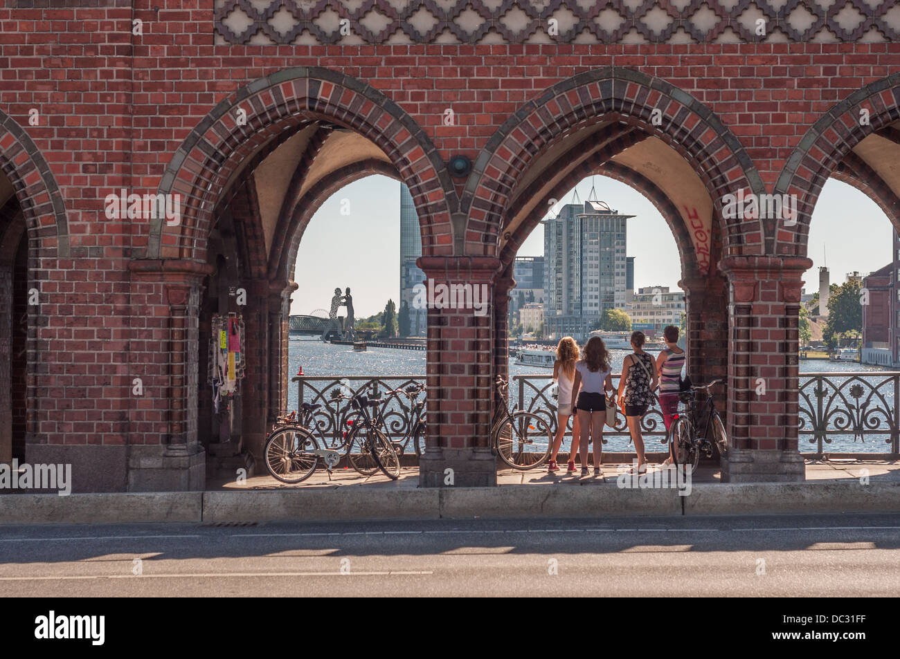 Young women with bicycles standing on the Oberbaum Bridge looking at the Spree River and the Molecule Man sculpture Stock Photo