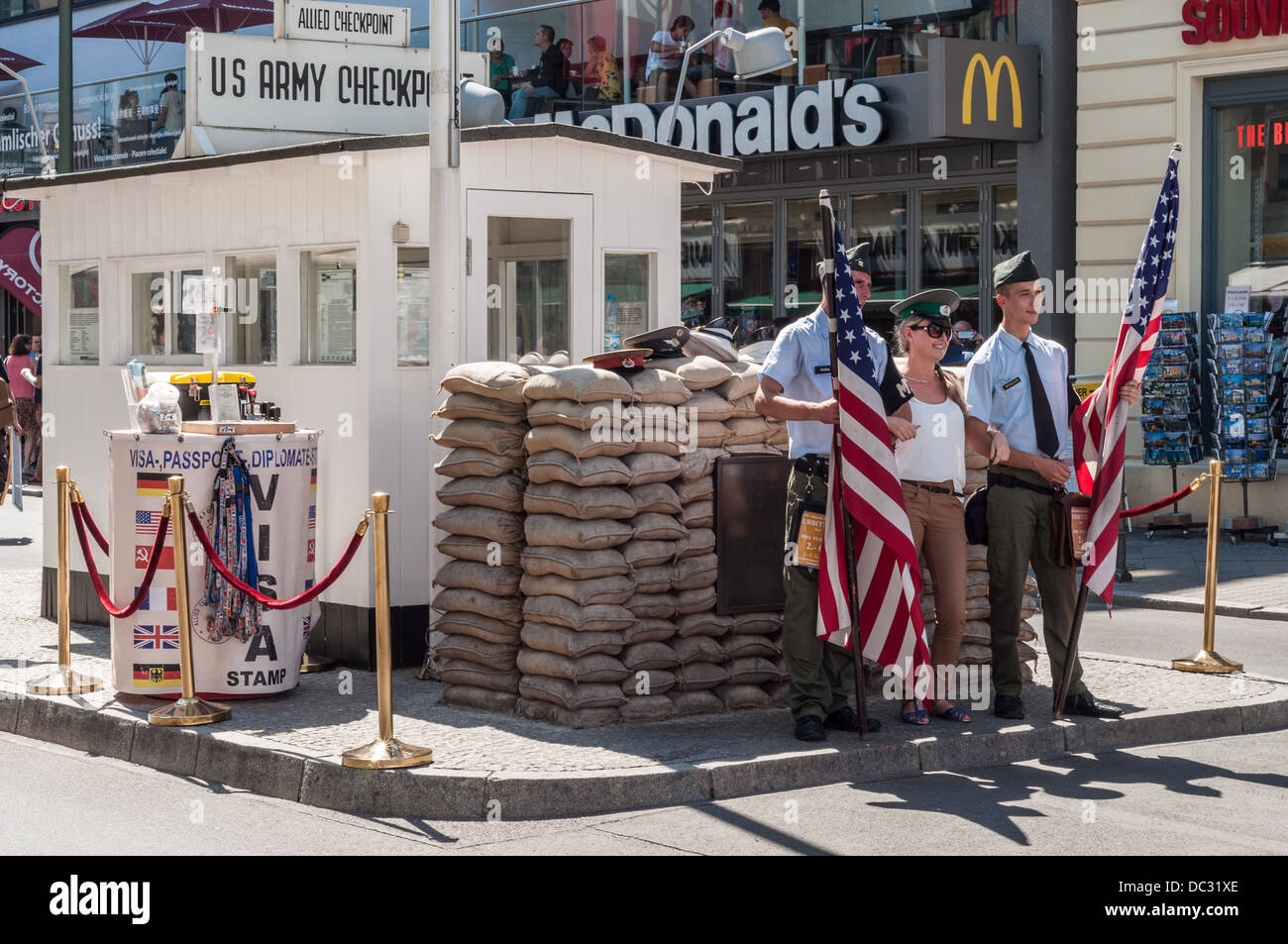 US Army Checkpoint Charlie – woman with visor cap and actors in American soldiers uniform posing - Berlin Germany Stock Photo