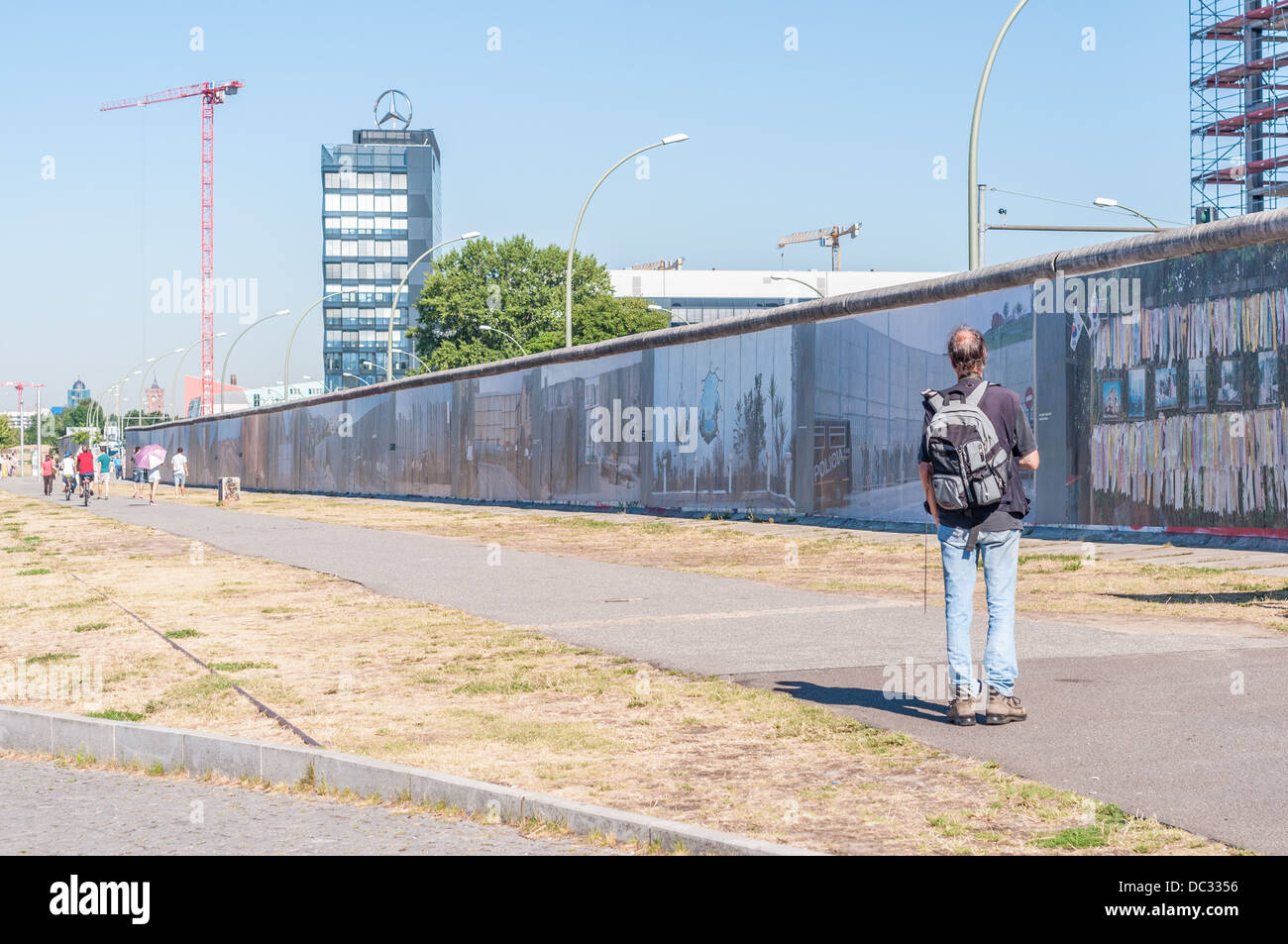 Man Looking At The Berlin Wall East Side Gallery Symbol Of The