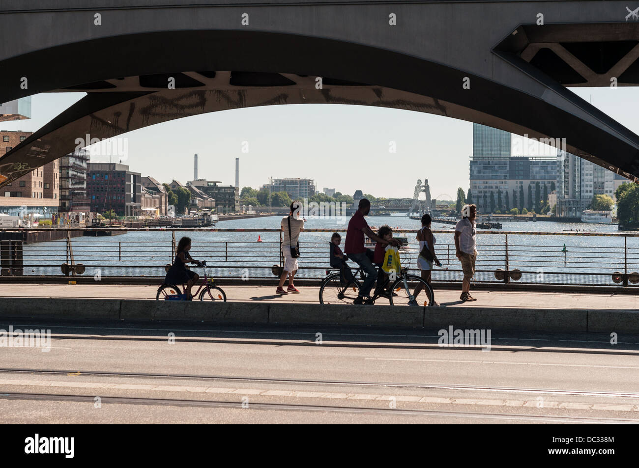 People with bicycles standing on the Oberbaum Bridge looking at the Spree River and the Molecule Man sculpture Stock Photo