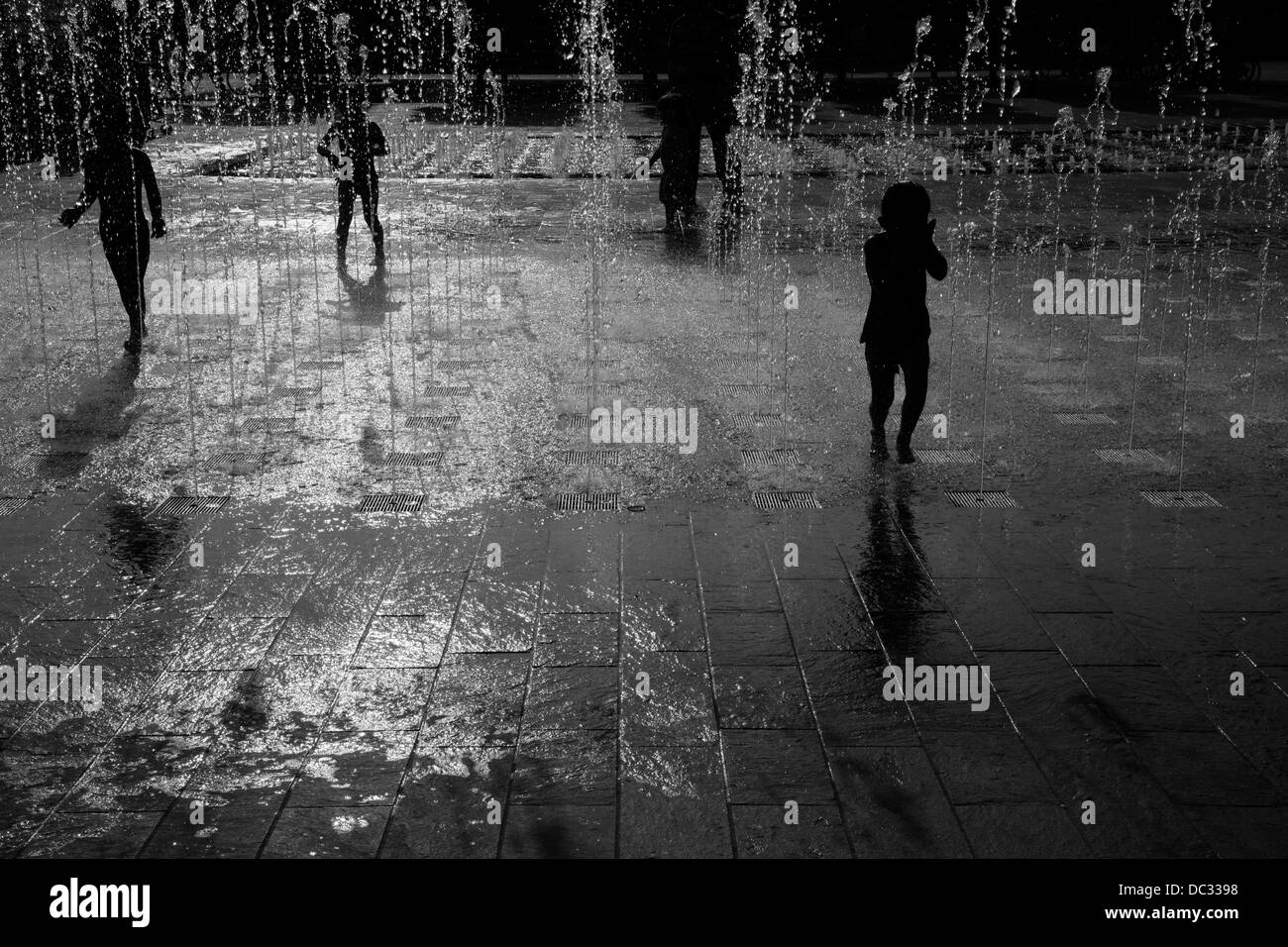 Children play in the fountains in Granary Square, King's Cross, London, UK - Stock Image