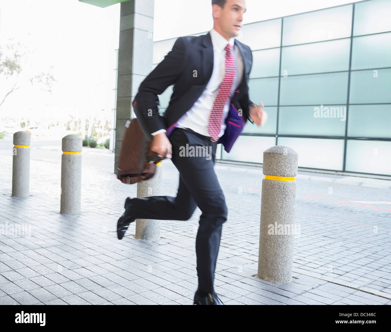 Businessman with briefcase running - Stock Image