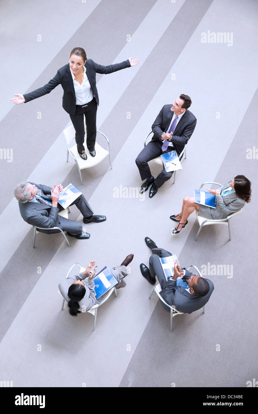 High angle view of businesswoman standing on chair in circle with co-workers - Stock Image