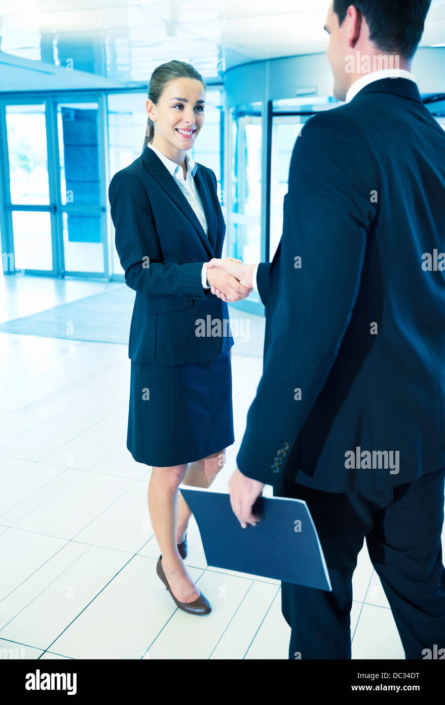 Smiling businessman and businesswoman handshaking in lobby - Stock Image