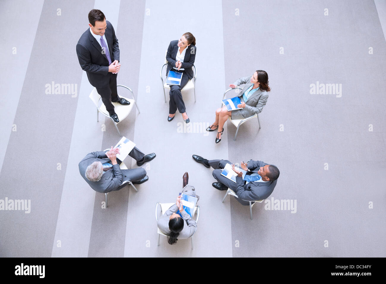 High angle view of businessman standing on chair in circle with co-workers - Stock Image
