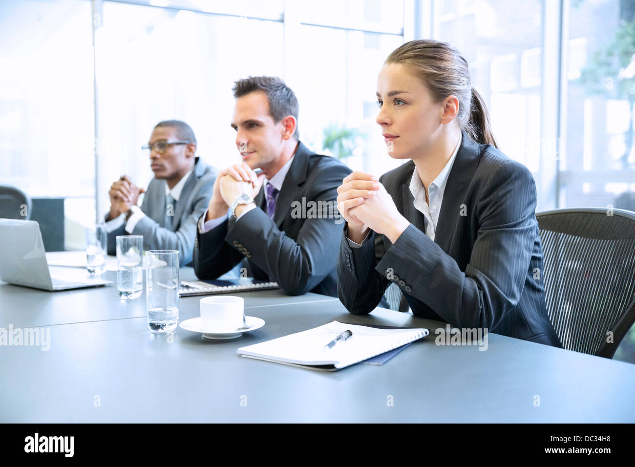 Attentive business people with hands clasped in meeting - Stock Image