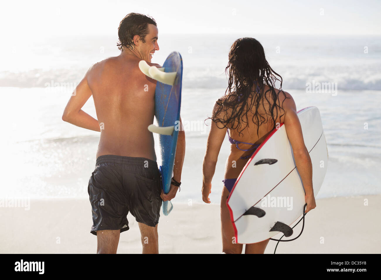 Couple walking with surfboards on beach - Stock Image