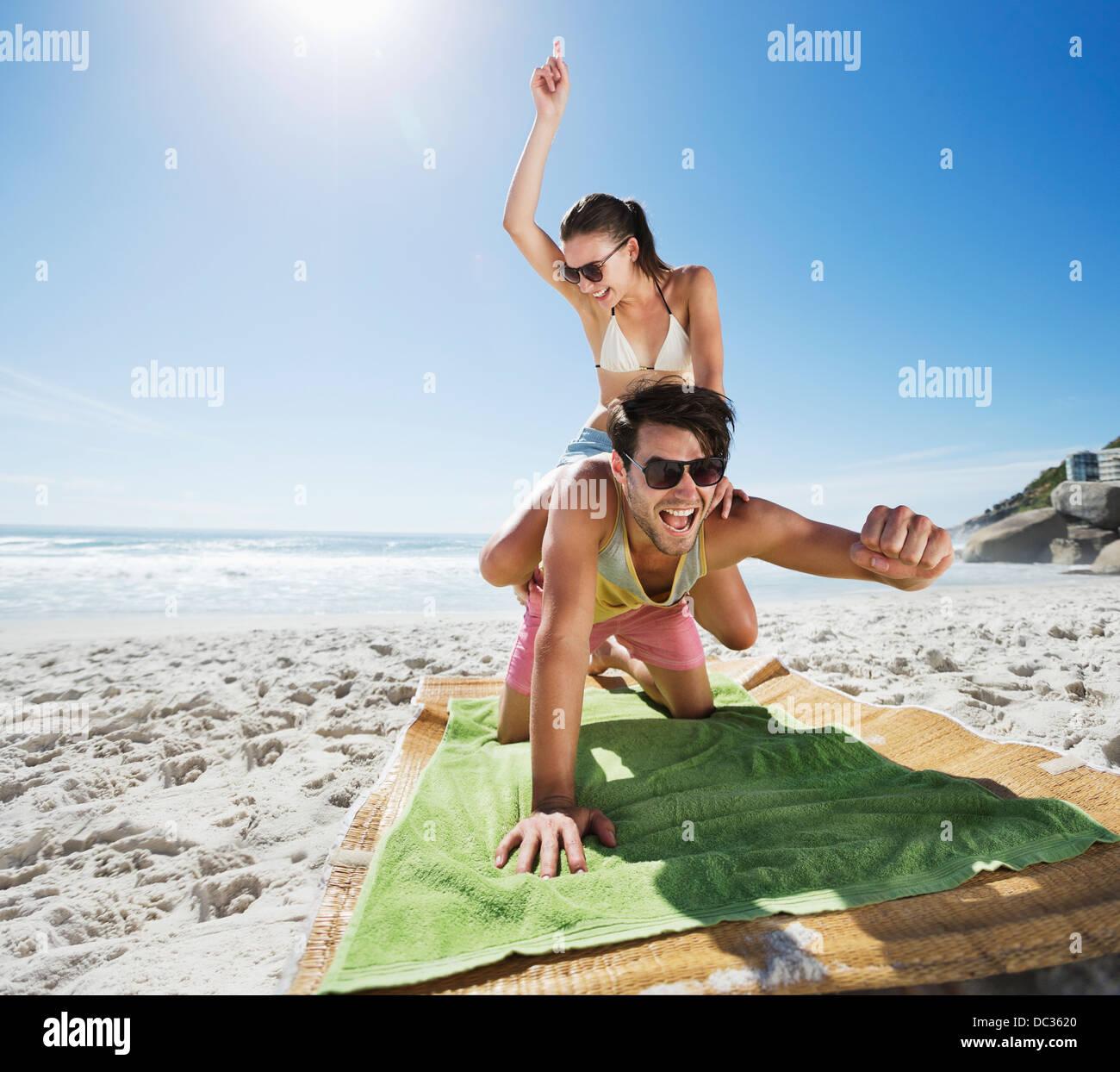 Woman piggybacking enthusiastic man on beach - Stock Image