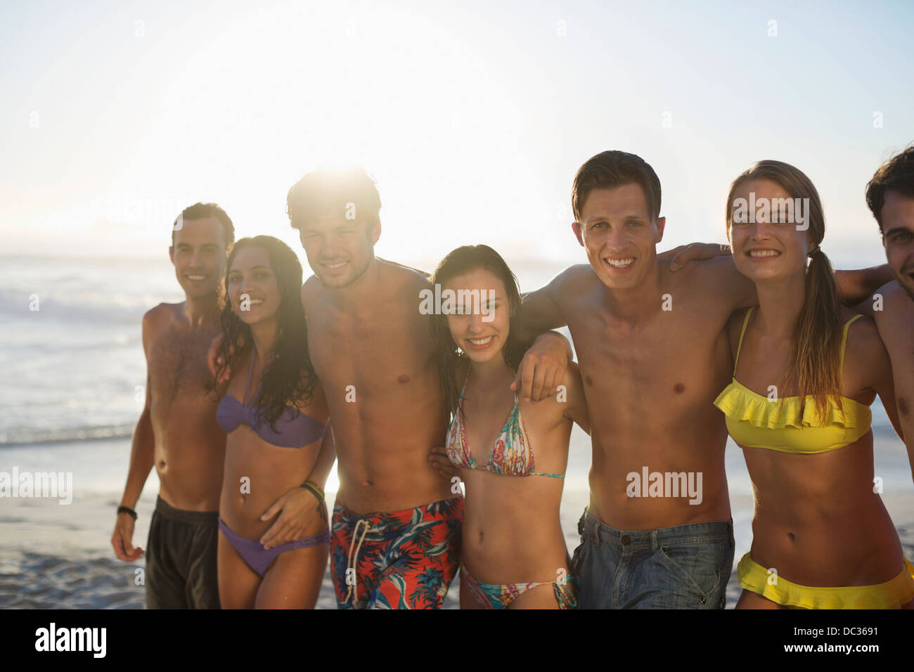 Portrait of friends in bikinis and swim trunks on beach - Stock Image