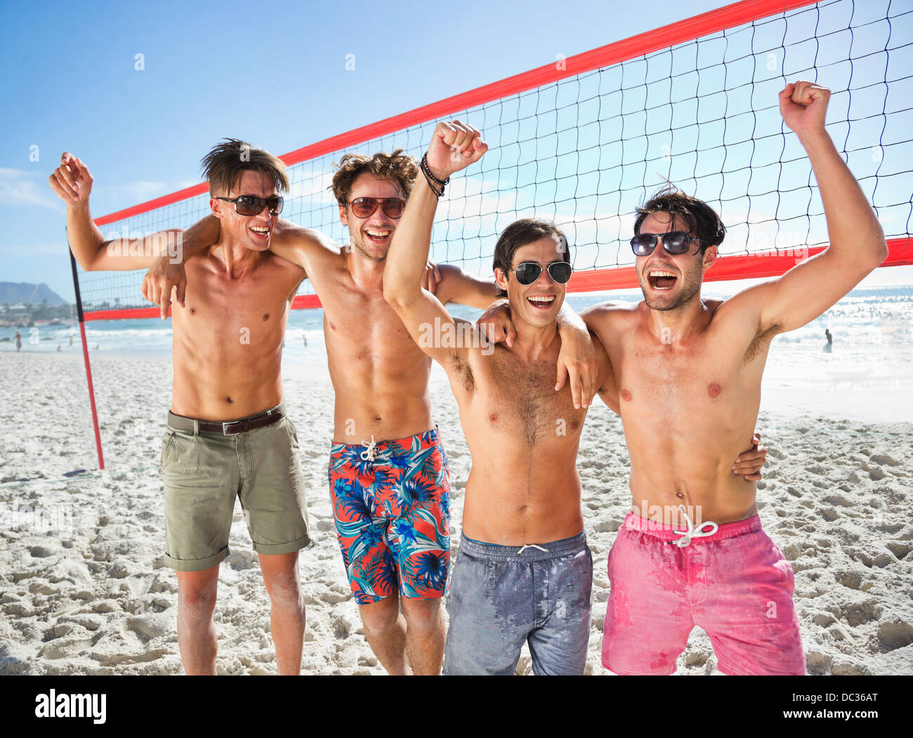 Portrait of enthusiastic friends on beach volleyball court - Stock Image