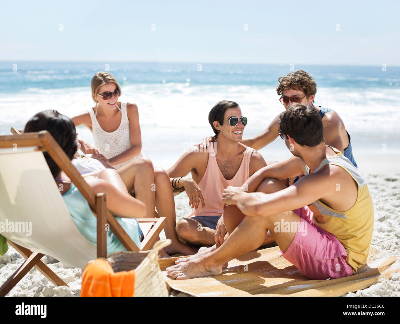 Friends hanging out on beach - Stock Image