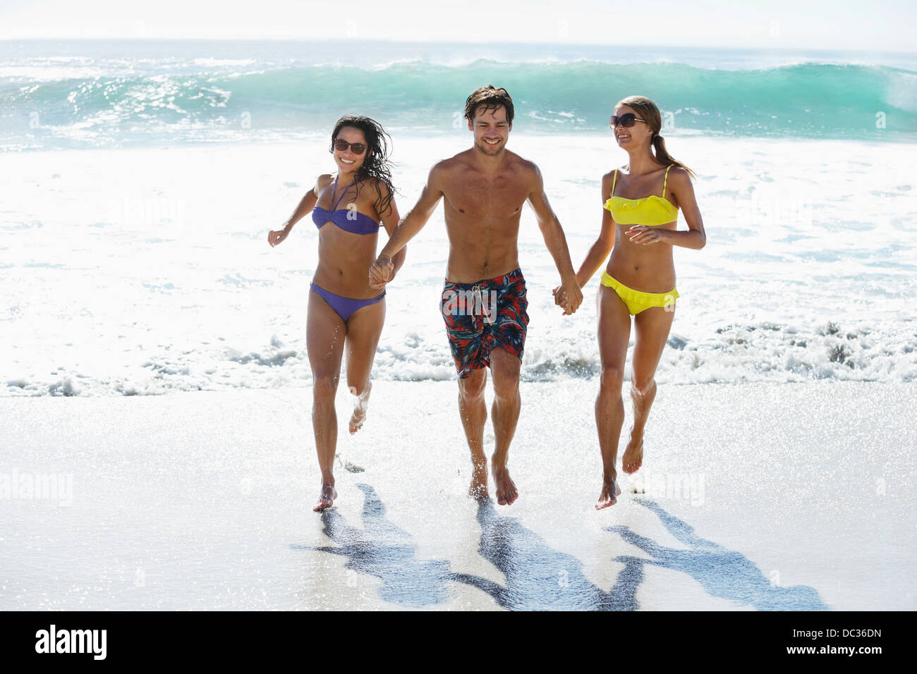 Friends holding hands and running on beach - Stock Image