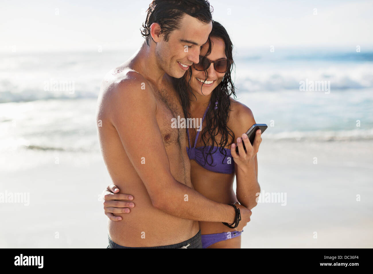 Happy couple with cell phone hugging on beach - Stock Image
