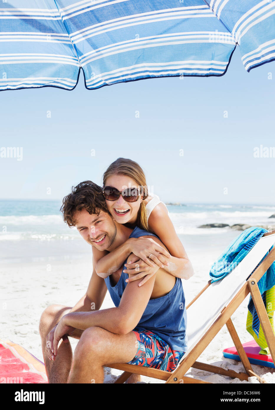 Portrait of happy couple hugging at beach - Stock Image