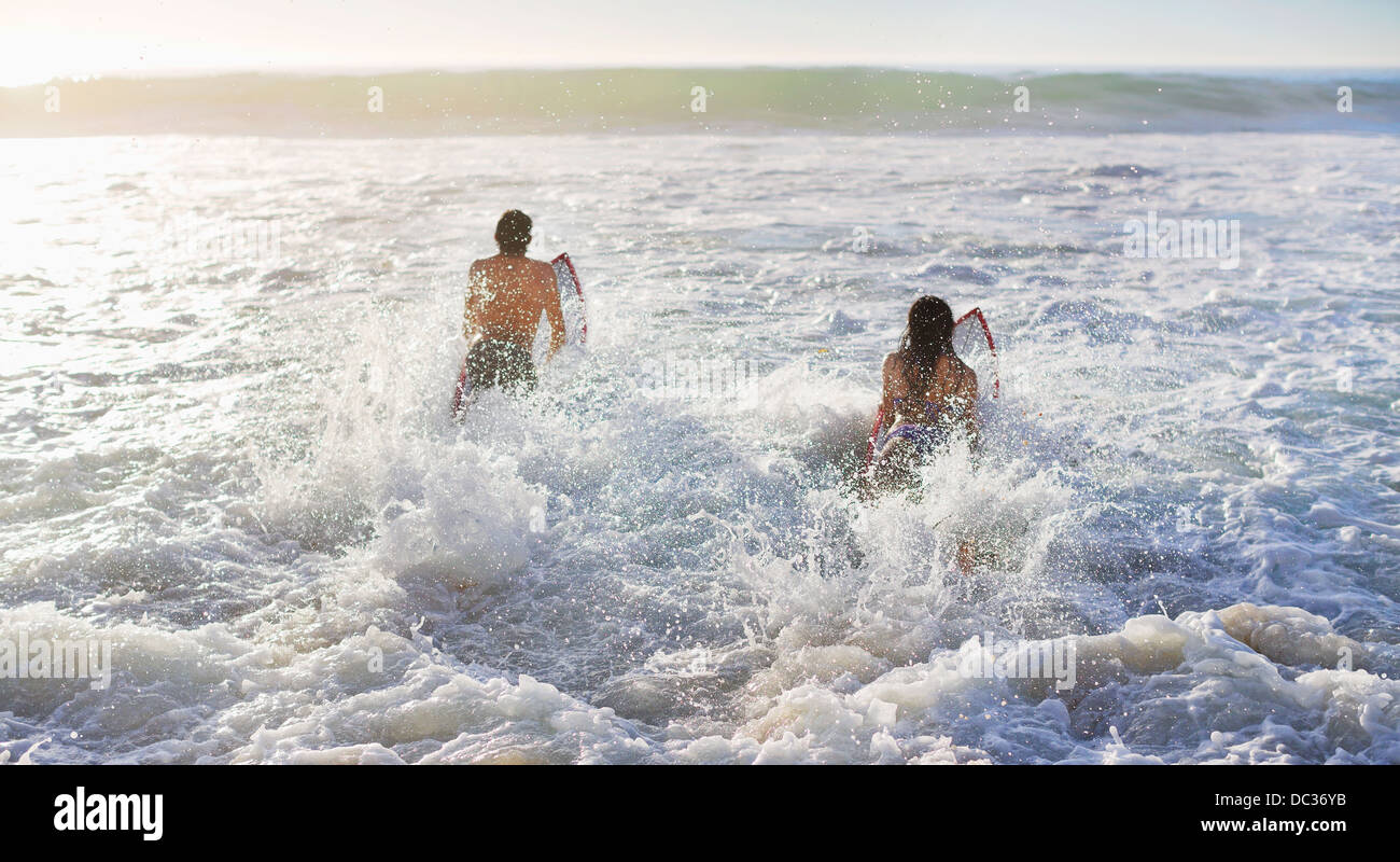Couple surfing in ocean - Stock Image