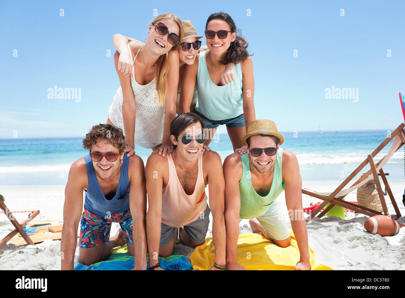 Portrait of happy friends forming pyramid on beach - Stock Image